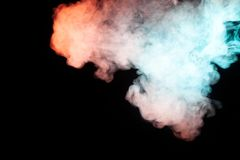 Background of colored smoke of turquoise, green and red color, s. Oaring at the top in the form of a mystical figure resembling a man on a black background stock photography