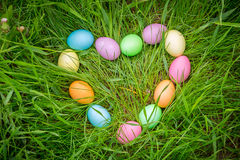 Background with colorful easter eggs on lawn in heart shape Royalty Free Stock Photo