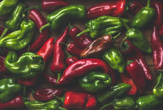 Background of colorful red and green bell peppers over wooden backdrop. Top view Royalty Free Stock Images