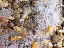Background from colorful sea pebbles, water and foam. Visible bubbles and sun glare Royalty Free Stock Photo