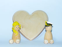 A background composed by a wooden family with a wooden hart to be customized for anniversaries. A wooden family on a soft background customizable for a wedding royalty free stock photos