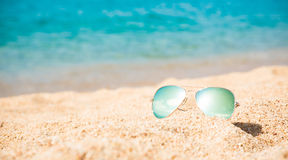 Background The concept of Rest Vacation. Beautiful background of Turquoise Sea with men`s sunglasses lying on the sand beach. The concept of Rest Vacation. Wide stock photo