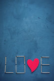 Background of concrete and blue paint plaster. On the texture matches arranged in the form of the word Love. In the middle o. F the letters have a wooden red royalty free stock photography