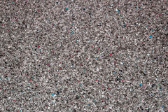 Background of concrete dark gray wall and multi-colored gravel with texture. Horizontal frame Royalty Free Stock Image