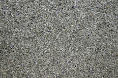 Background of concrete dark gray wall and multi-colored gravel w Royalty Free Stock Photo
