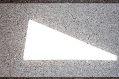 Background of a concrete wall and multi-colored gravel with a texture and a sunlight flare in the form of a triangle in the middle Royalty Free Stock Photos
