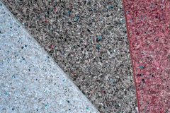 Background of a concrete wall and multi-colored gravel with a texture of three parts - white, gray and red. Horizontal frame Royalty Free Stock Photography