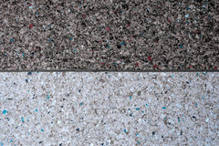 Background of a concrete wall and multi-colored gravel with a texture of two parts - white and gray. Horizontal frame Royalty Free Stock Image