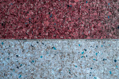Background of a concrete wall and multi-colored gravel with a texture of two parts - white and red. Horizontal frame Royalty Free Stock Image