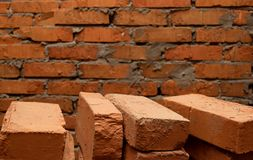 Background consisting of a brick wall and several bricks in the foreground. Background of a brick wall and several bricks in the foreground Stock Photos