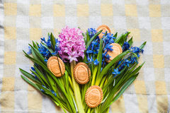 Background with cookies in the shape of Easter eggs in the blue snowdrops on checkered kitchen towel Stock Photography