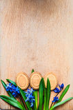 Background with cookies the shape of Easter eggs in the blue snowdrops on a wooden chopping board Stock Images