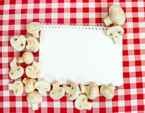 Background for cooking recipes. Mushrooms around blank paper Stock Images
