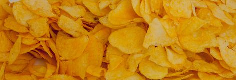 Background corrugated golden chips with texture. A variety of potato chips background. Background corrugated golden chips with. Texture stock images