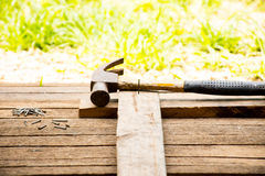 Background Craftsman tool  with old hammer and Small nails on wooden background and outdoor view country style. Royalty Free Stock Photo