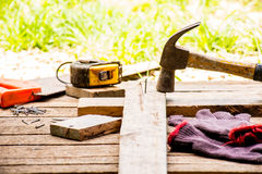 Background Craftsman tool and  old hammer and Small nails on wooden background and outdoor view country style. Royalty Free Stock Photography