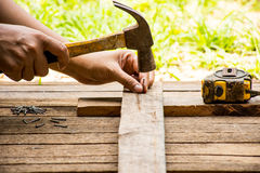 Background Craftsman tool with old hammer with tape measure and small nails and working outdoor view.Background for carpenter Stock Image