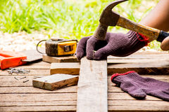Background Craftsman tool such as old hammer with tape measure and small nails and saw with glove and working outdoor view. Royalty Free Stock Images