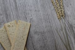 Background with crispbread of wheat grains and ears of wheat on a wooden background. Healthy food. Royalty Free Stock Photography