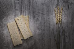 Background with crispbread of wheat grains and ears of wheat on a wooden background. Healthy food. Royalty Free Stock Image