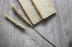 Background with crispbread of wheat grains and ears of wheat on a wooden background. Healthy food. Stock Photos