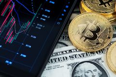 Bitcoin cryptocurrency and banknotes of one US dollar next to mobile phone showing candlestick chart. Background with cryptocurrency bitcoin on dollar bill and royalty free stock photo
