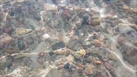 Background of a crystal water surface. Crystal wavy surface of water with light reflections in the sea, river or lake stock footage
