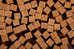 Background of cubes of brown sugar on a wooden table Royalty Free Stock Image
