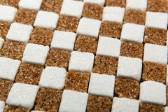 Background of cubes of brown and white sugar Royalty Free Stock Photos