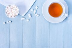 Background with cup of tea and marshmallow on the light blue woo. Den table, copy space Stock Photo