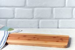 Background with cutting board on white wooden table and against the background a brick wall.  royalty free stock photos