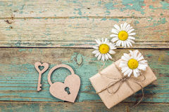 Background with daisies, gift box, lock-heart and key on old boa Royalty Free Stock Photos