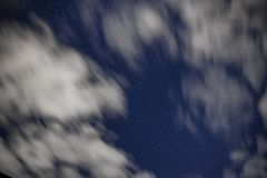 Background of dark-blue night sky with countless twinkle stars and moving white clouds upon on it Stock Images