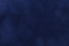 Background of dark blue suede fabric closeup. Velvet matt texture of navy blue nubuck textile.  stock photography