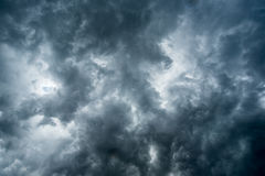 Background of dark clouds before a thunder-storm ,sunlight through very dark clouds background ,White Hole in the Whirlwind of dar Stock Photos