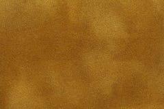 Background of dark golden suede fabric closeup. Velvet matt texture of yellow nubuck textile royalty free stock photography