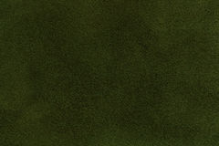 Background of dark green suede fabric closeup. Velvet matt texture of olive nubuck textile. Background of dark green suede fabric closeup. Velvet matt texture of Royalty Free Stock Image