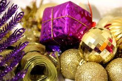 Christmas and New Years background is decorated with glittering gold balls and lilac color square gift, lilac bird among. Colorful Christmas and new year stock photos