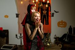 Beautiful young woman with child with pumpkins autumn. Smiling mother and son. Cute happy little devil and young mother royalty free stock photo
