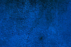 Background of a deep blue stucco coated and painted exterior, rough cast of cement and concrete wall Stock Image