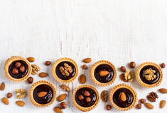 Background desserts Nutty chocolate dessert small tarts Stock Images