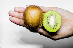 Healthy eating and diet Topic: Human hand holding a half kiwi isolated on a white background in the studio. Background diet eating half hand healthy holding royalty free stock images