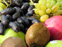 Fruits Background. A background of different fresh fruits like yellow grapes, kiwi, apple and black grapes Stock Photos