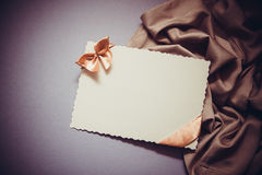 Background with drapery. White postcard with beige bow for text Stock Image