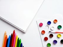 Background with drawing book, crayons and watercolor paints. School tools and materials, education and knowledge, art in design and creativity royalty free stock image