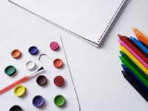 Background with drawing book, crayons and watercolor paints. School tools and materials, education and knowledge, art in design and creativity royalty free stock photos