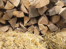 Background of dry chopped firewood logs and hay Royalty Free Stock Photo