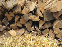 Background of dry chopped firewood logs and hay Stock Photos