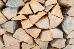 Background of dry chopped firewood logs in a pile. Natural wooden background, closeup of chopped firewood. Firewood stacked and prepared for winter Pile of wood Stock Images