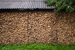 Background of dry chopped firewood logs in a pile. Wall firewood near the house. under roof stock image